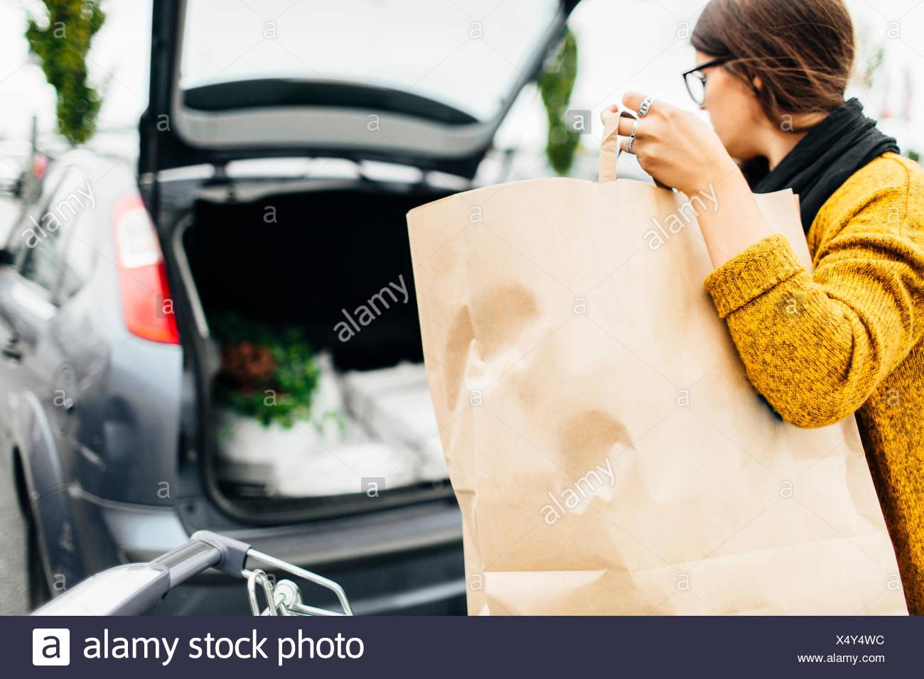 Jeune femme loading panier dans coffre de voiture Photo Stock