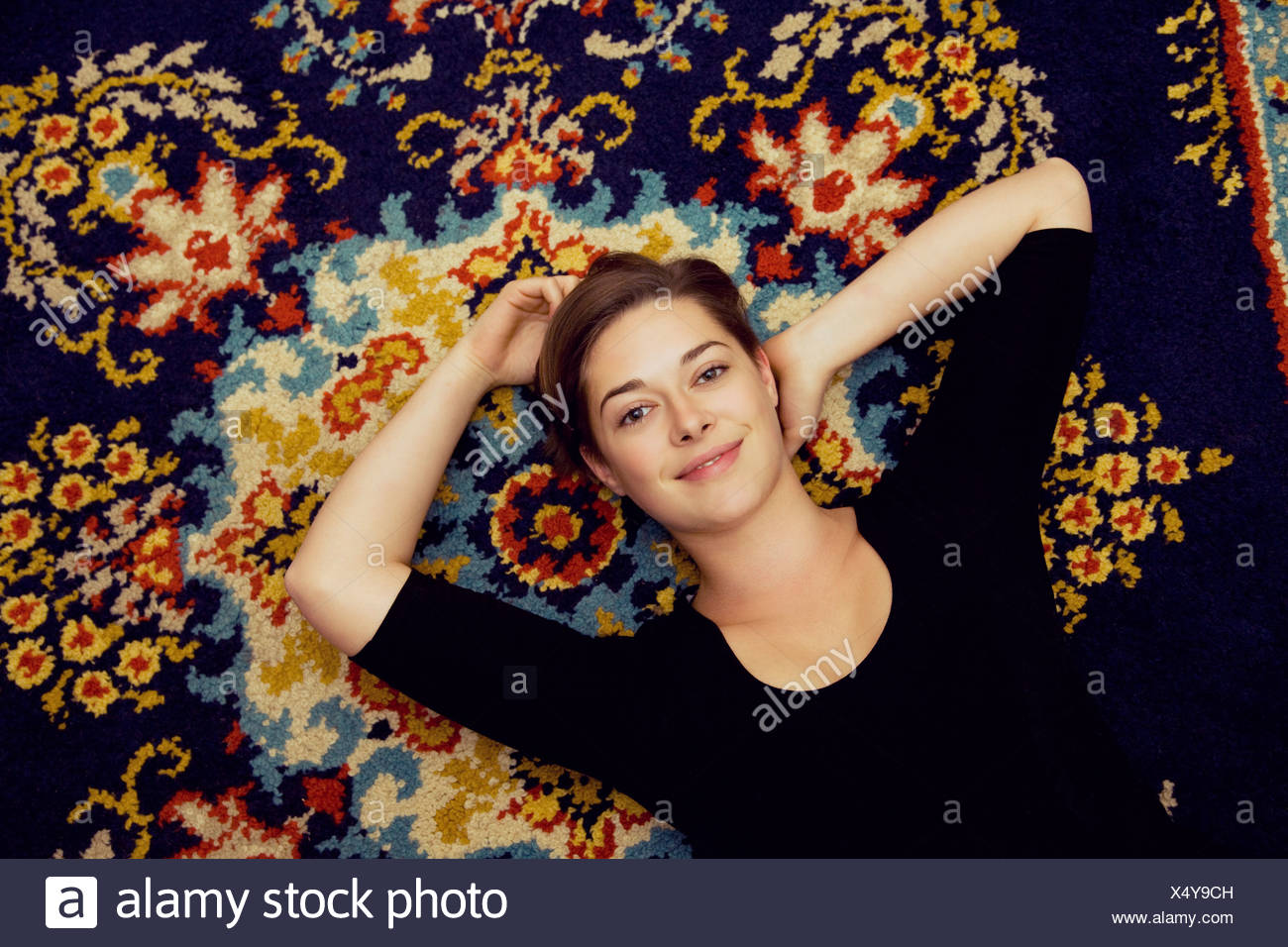 Portrait of young woman lying on tapis à motifs Photo Stock