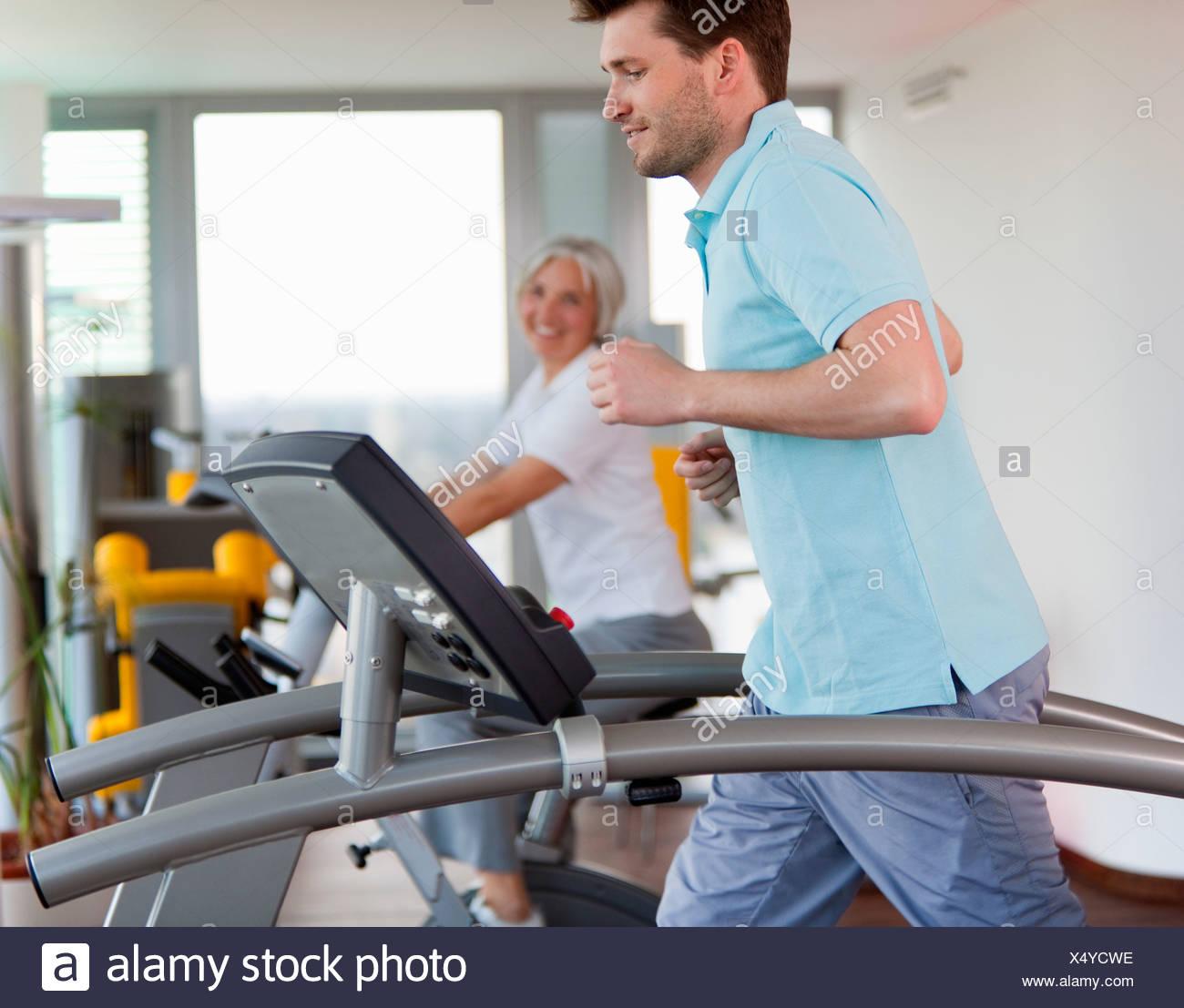 L'homme à l'aide de tapis roulant dans une salle de sport Banque D'Images