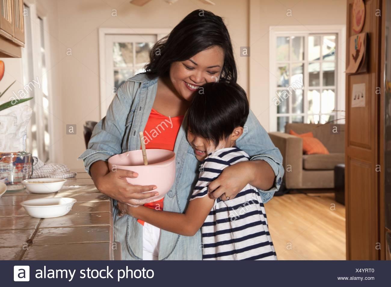 Boy hugging mère dans la cuisine Photo Stock