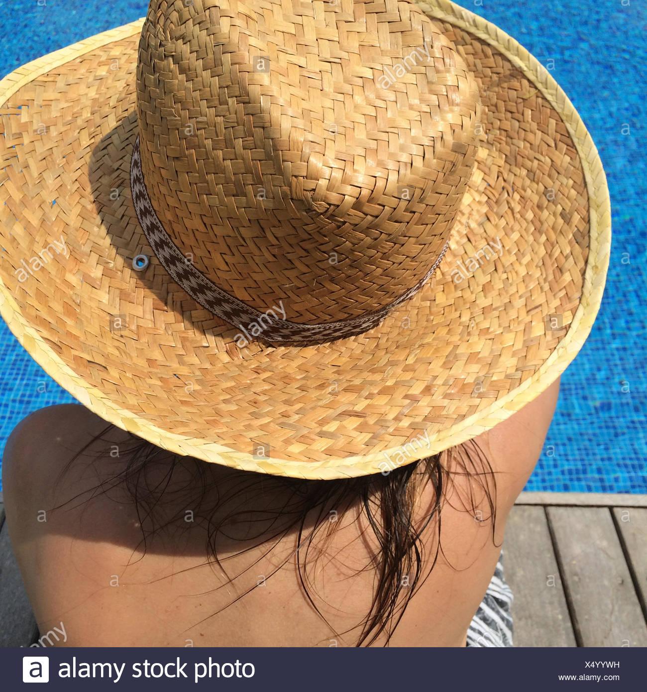 Femme au chapeau de soleil assis par piscine Photo Stock