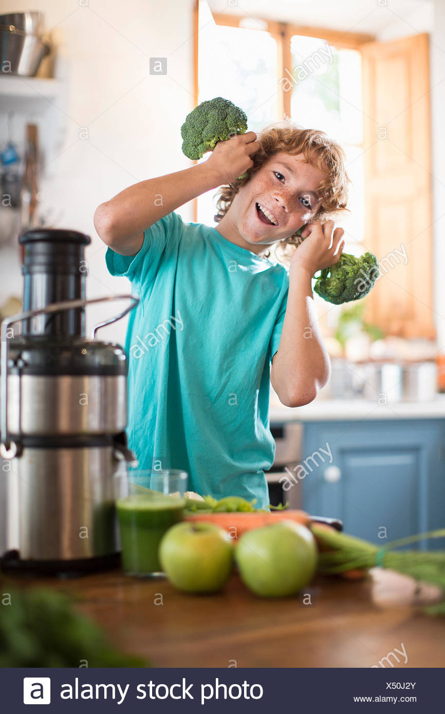Teenage boy playing with broccoli in kitchen Photo Stock