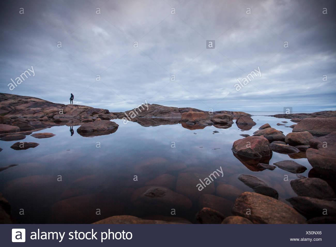 Femme debout par un rocher en mer, piscine Suède Photo Stock