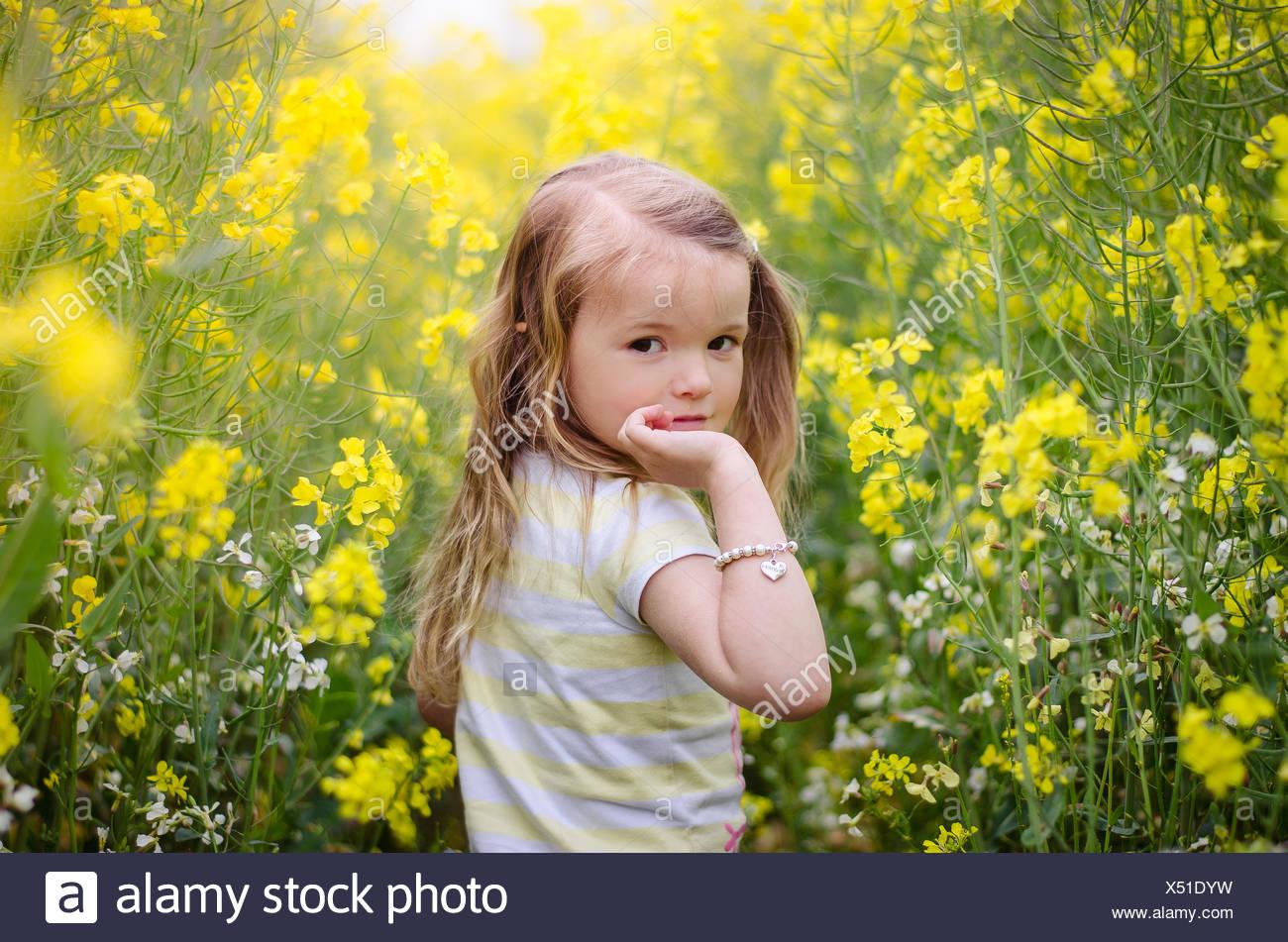 À la fille par-dessus son épaule dans un pré de fleurs jaunes Photo Stock