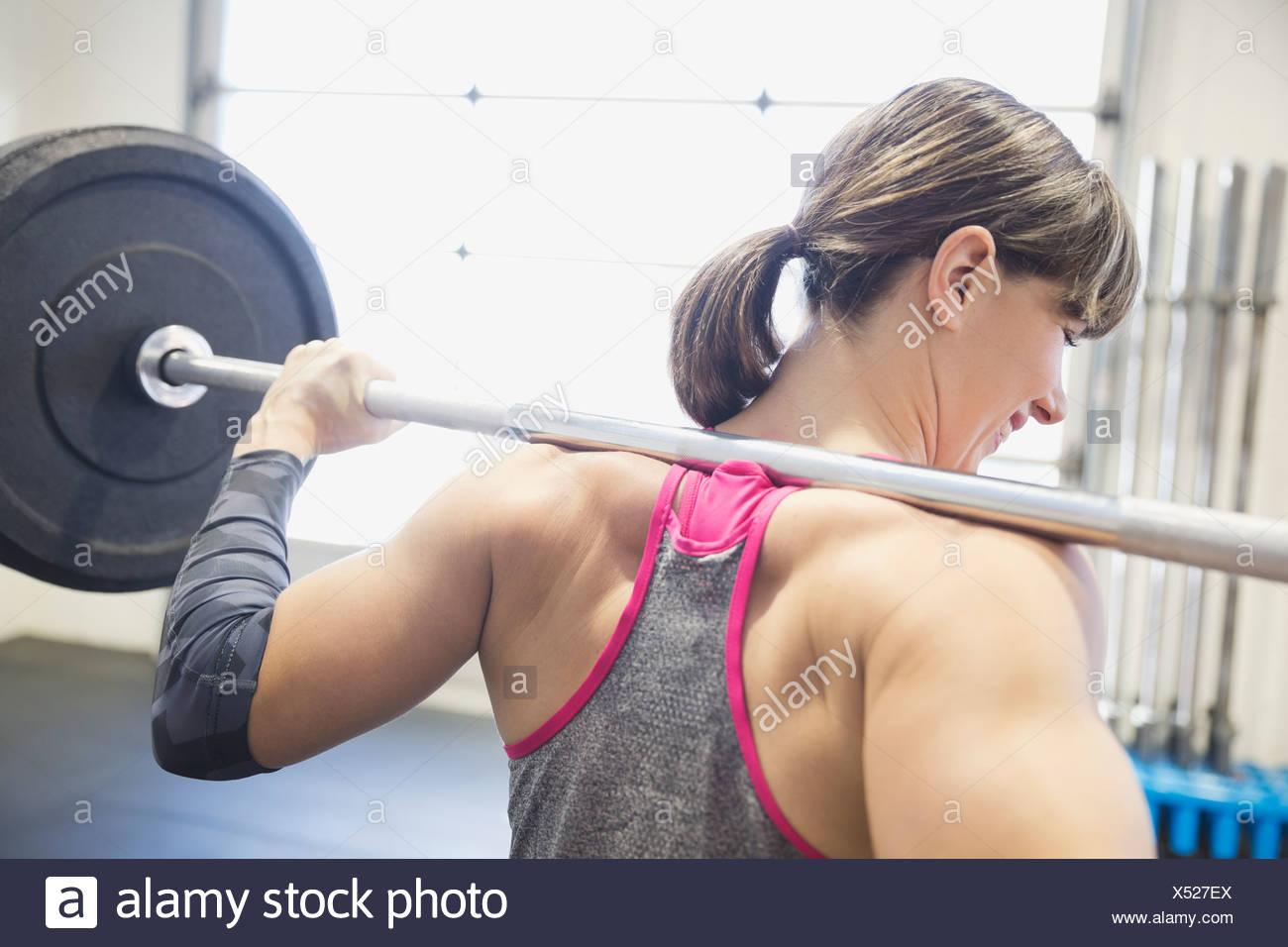 Femme debout avec haltère long sur les épaules Photo Stock
