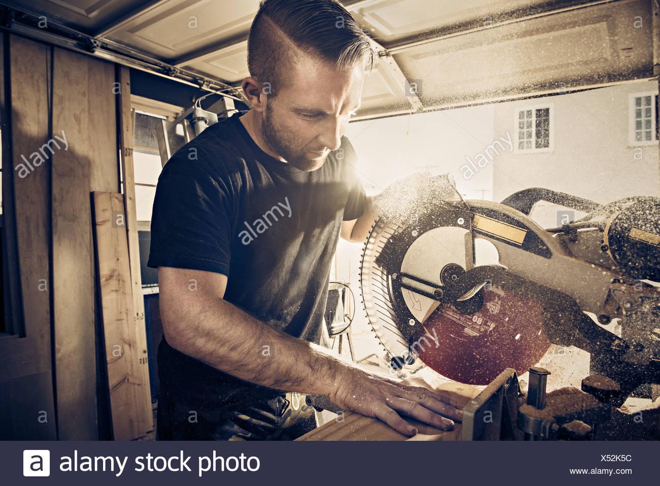 Male carpenter planche de bois de sciage en atelier Photo Stock