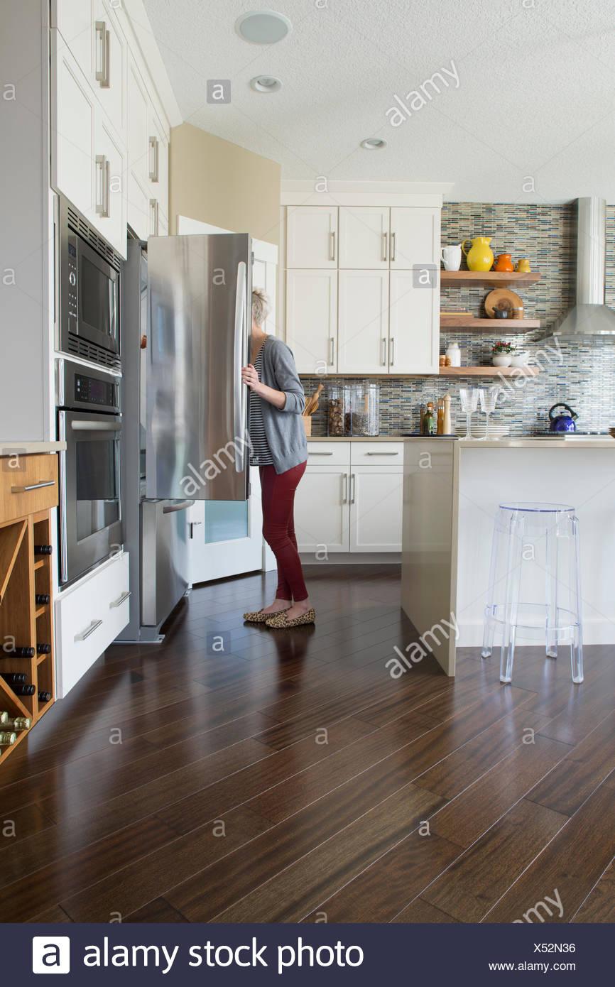Woman peering dans réfrigérateur dans la cuisine Photo Stock