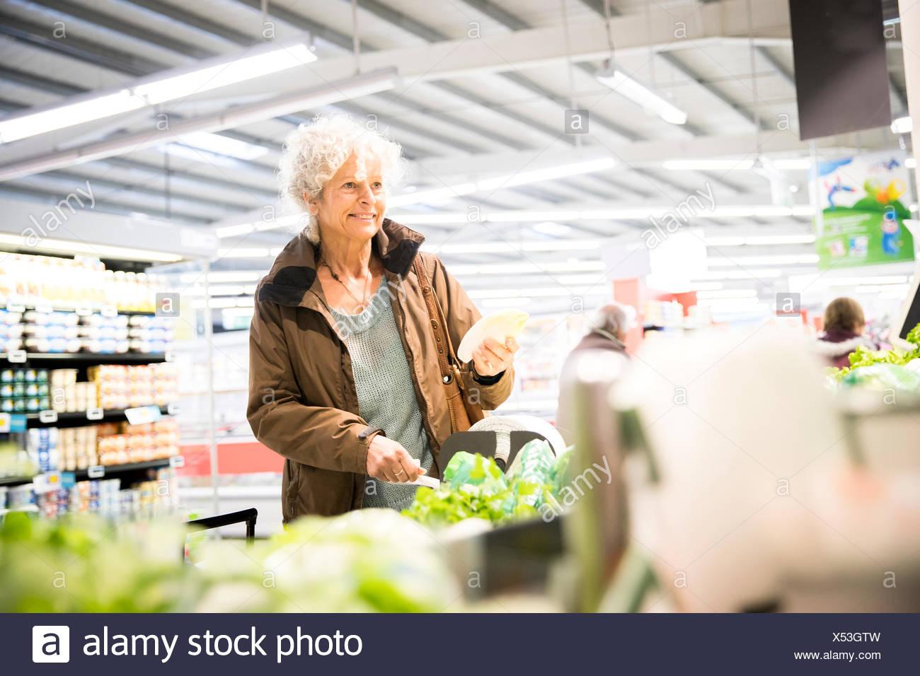 Femme mature en supermarché, à la recherche de produits frais Photo Stock