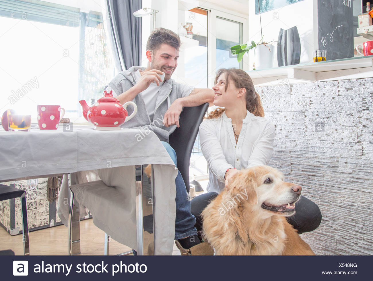 Young couple having breakfast, avec chien Photo Stock