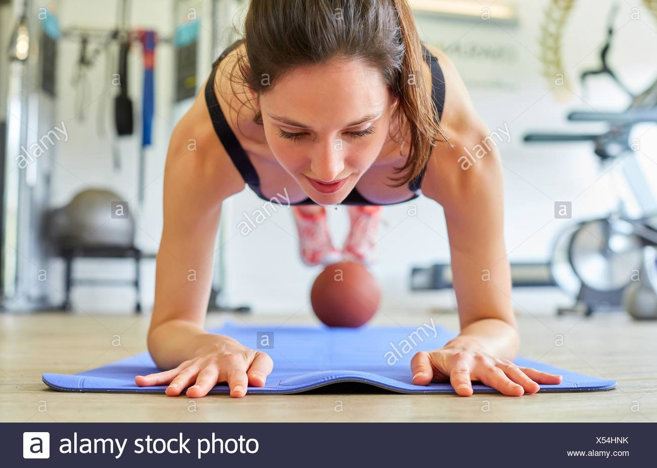 Femme faisant des tractions avec ball in gym Photo Stock