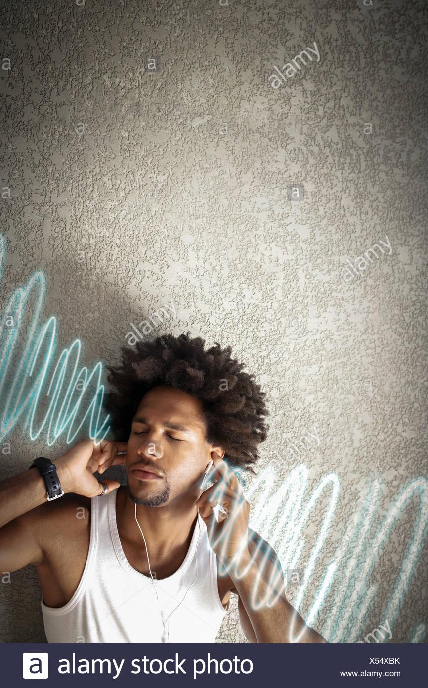 Jeune homme écoute détendue de la musique tout en se penchant sur le mur Photo Stock