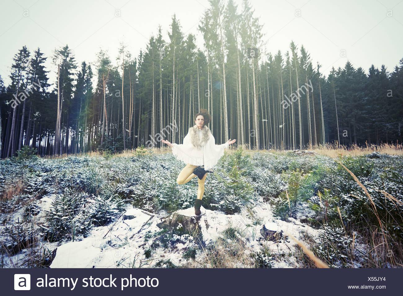 Mid adult woman practicing yoga l'arbre sur pied en forêt Banque D'Images