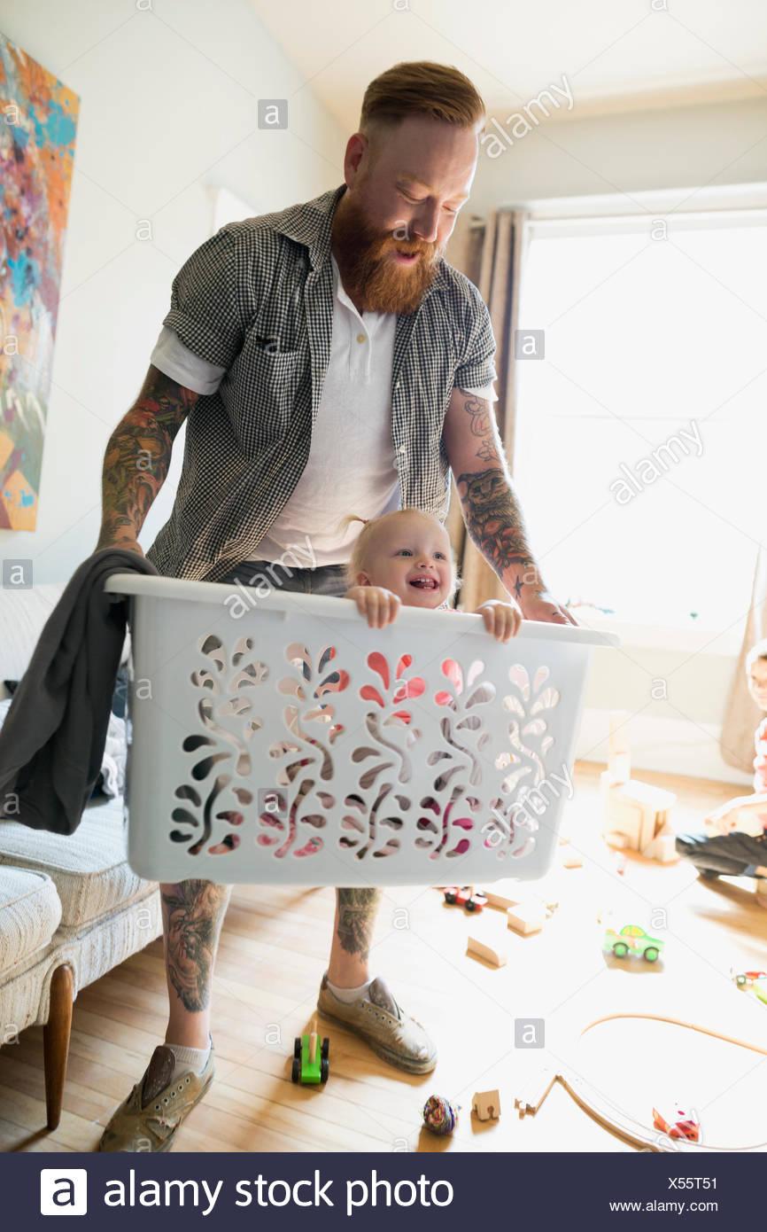 Père exerçant son heureux fille dans panier de blanchisserie Photo Stock