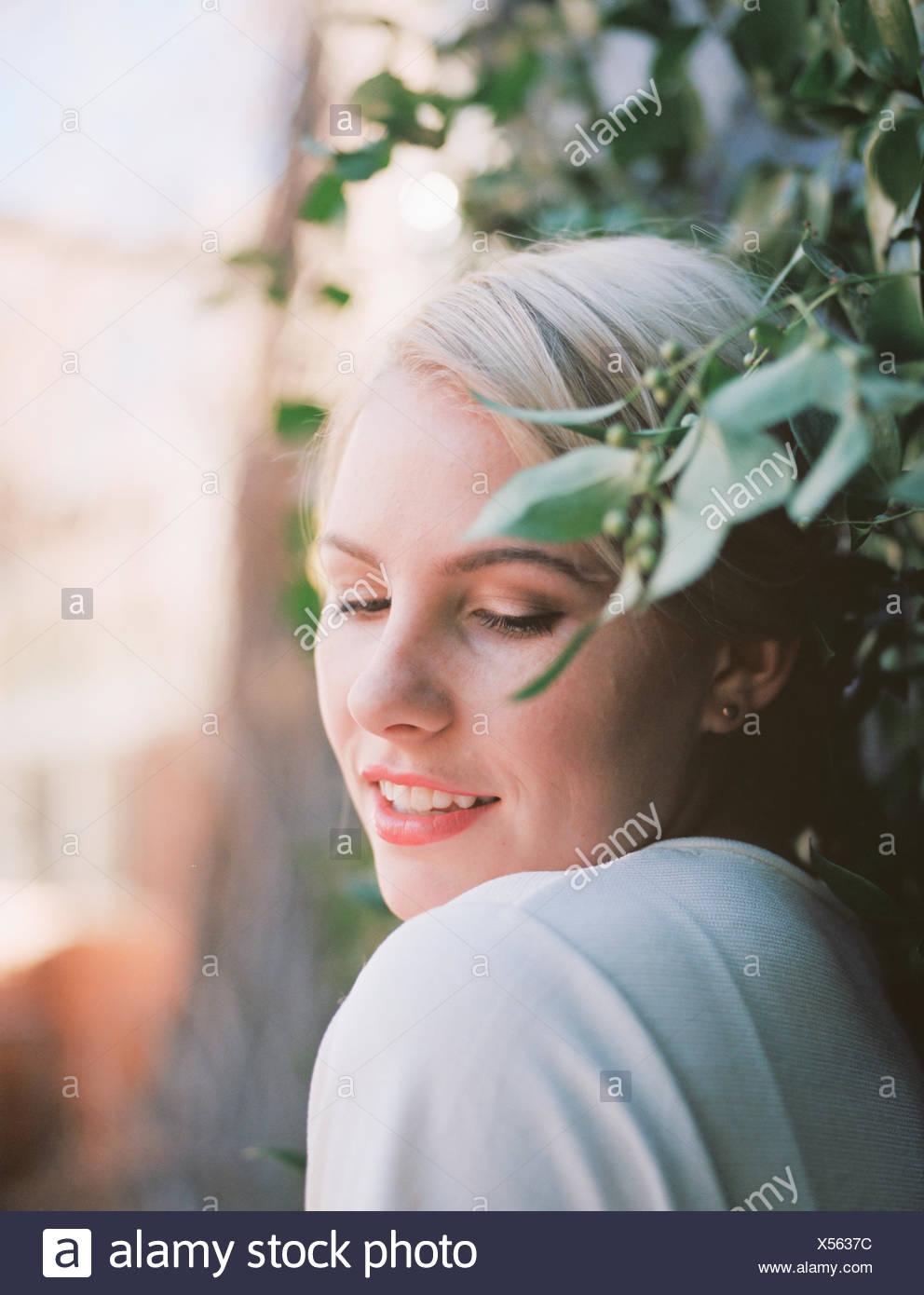 Une jolie femme avec un demi-sourire, appuyé contre un mur d'une vigne. Photo Stock