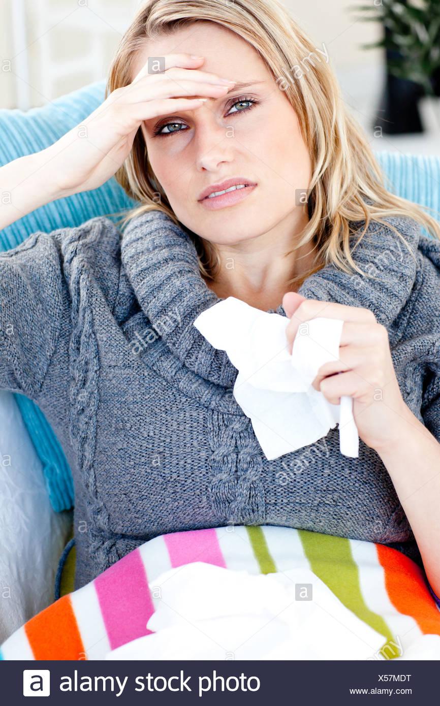 Downcast femme couchée sur un canapé avec les tissus et se sentir sa température Photo Stock
