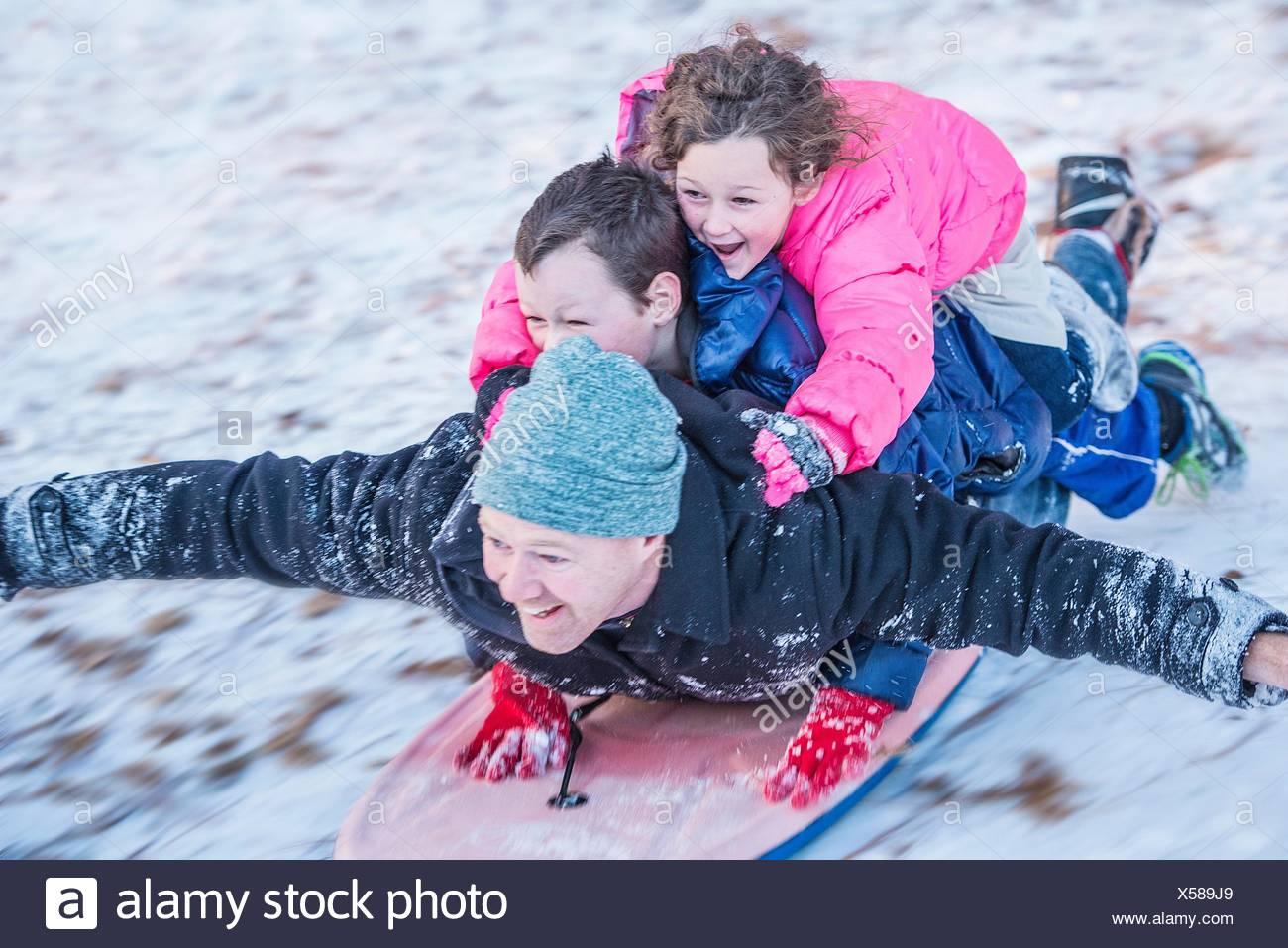 Portrait du père, son fils et sa fille portant sur le dessus de l'autre circonscription en bas de la colline de traîneau Banque D'Images