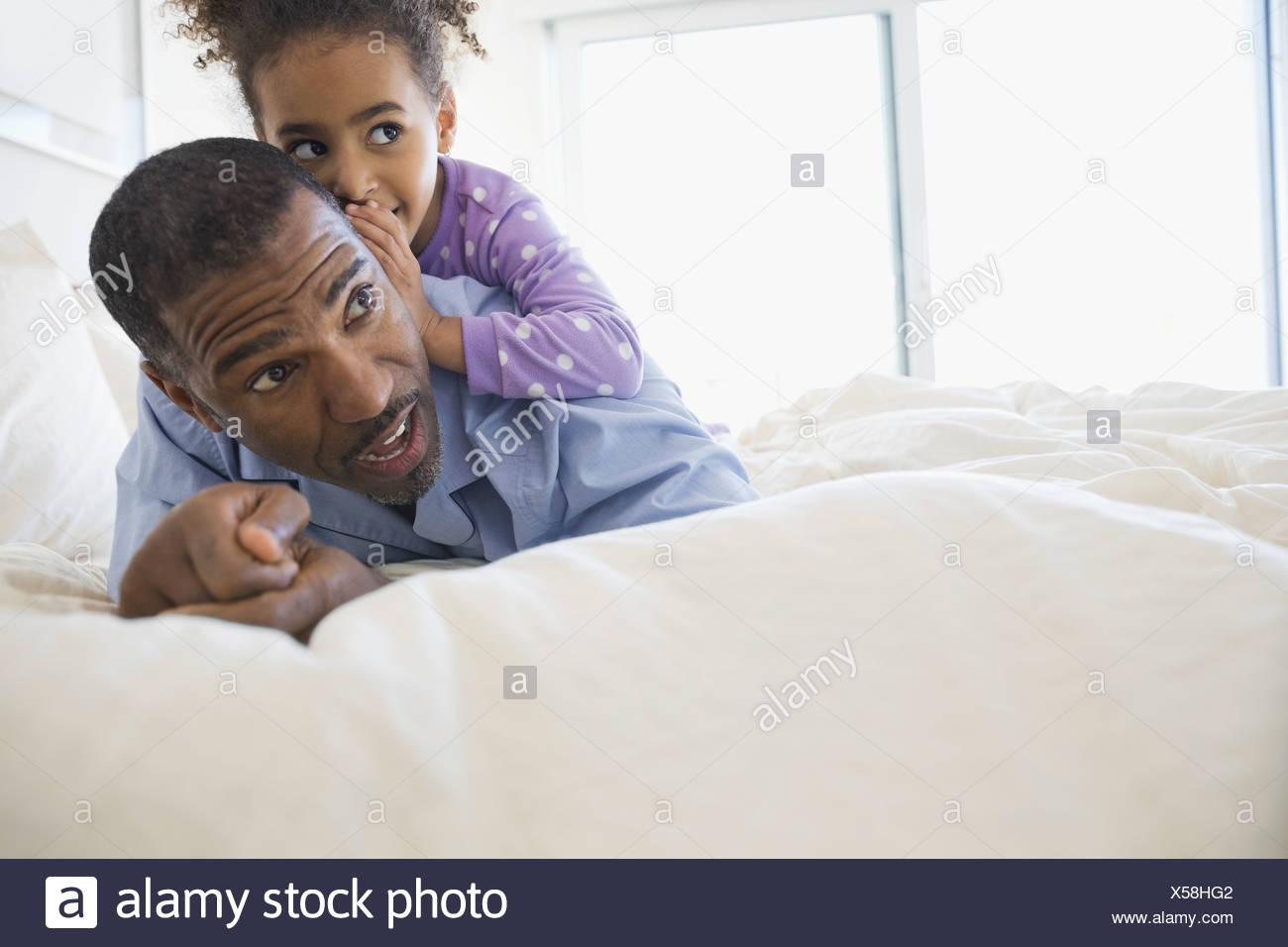 Fille chuchoter dans l'oreille de pères Photo Stock