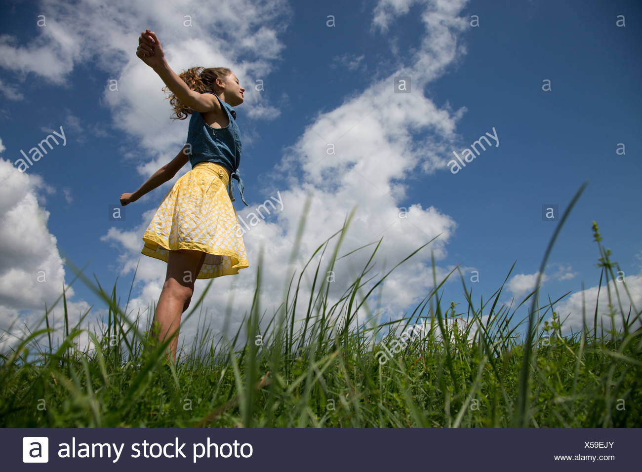 Teenage Girl standing with arms outstretched in field Banque D'Images