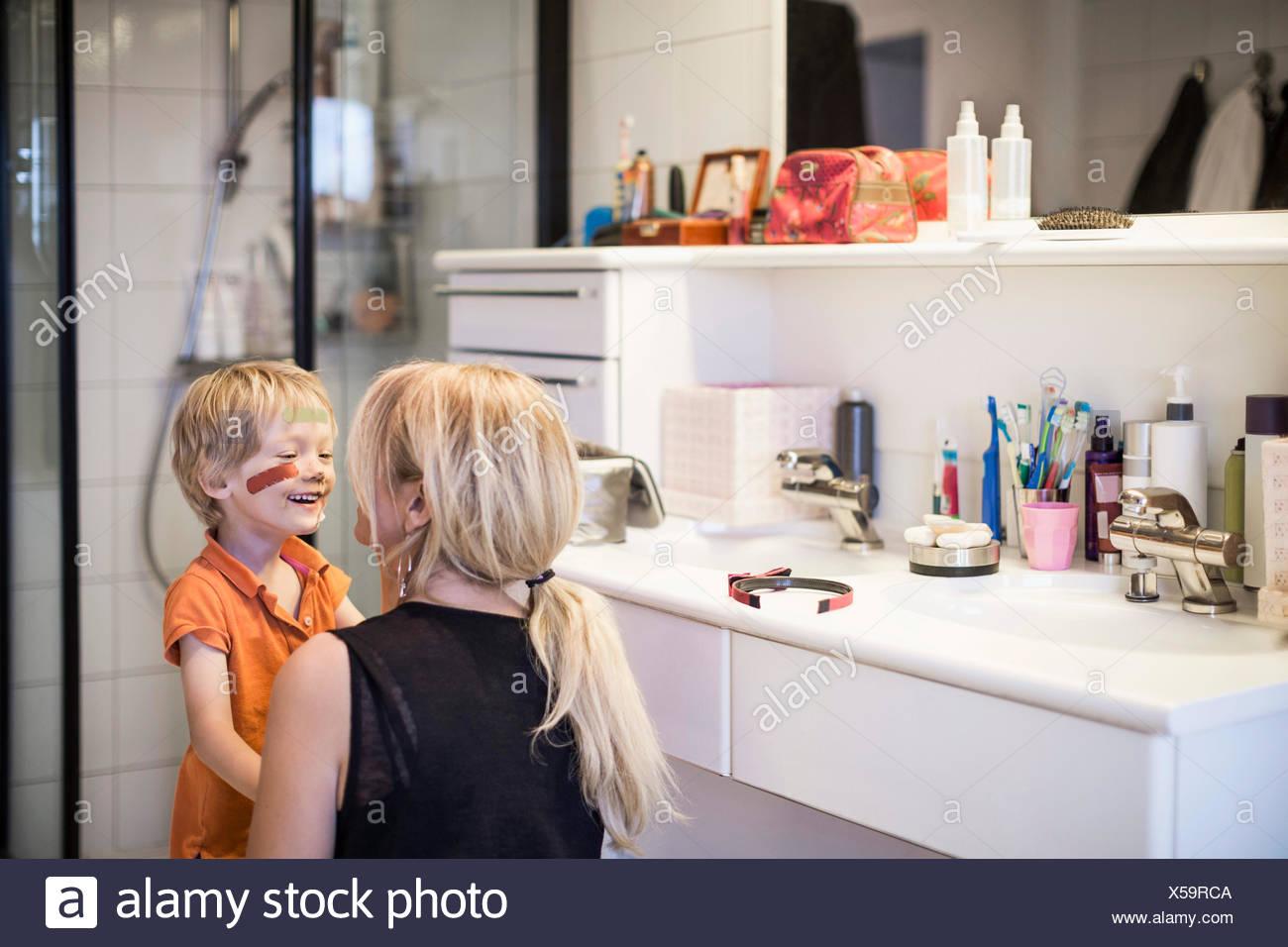 Femme à la recherche du fils au visage blessé dans la salle de bains Photo Stock