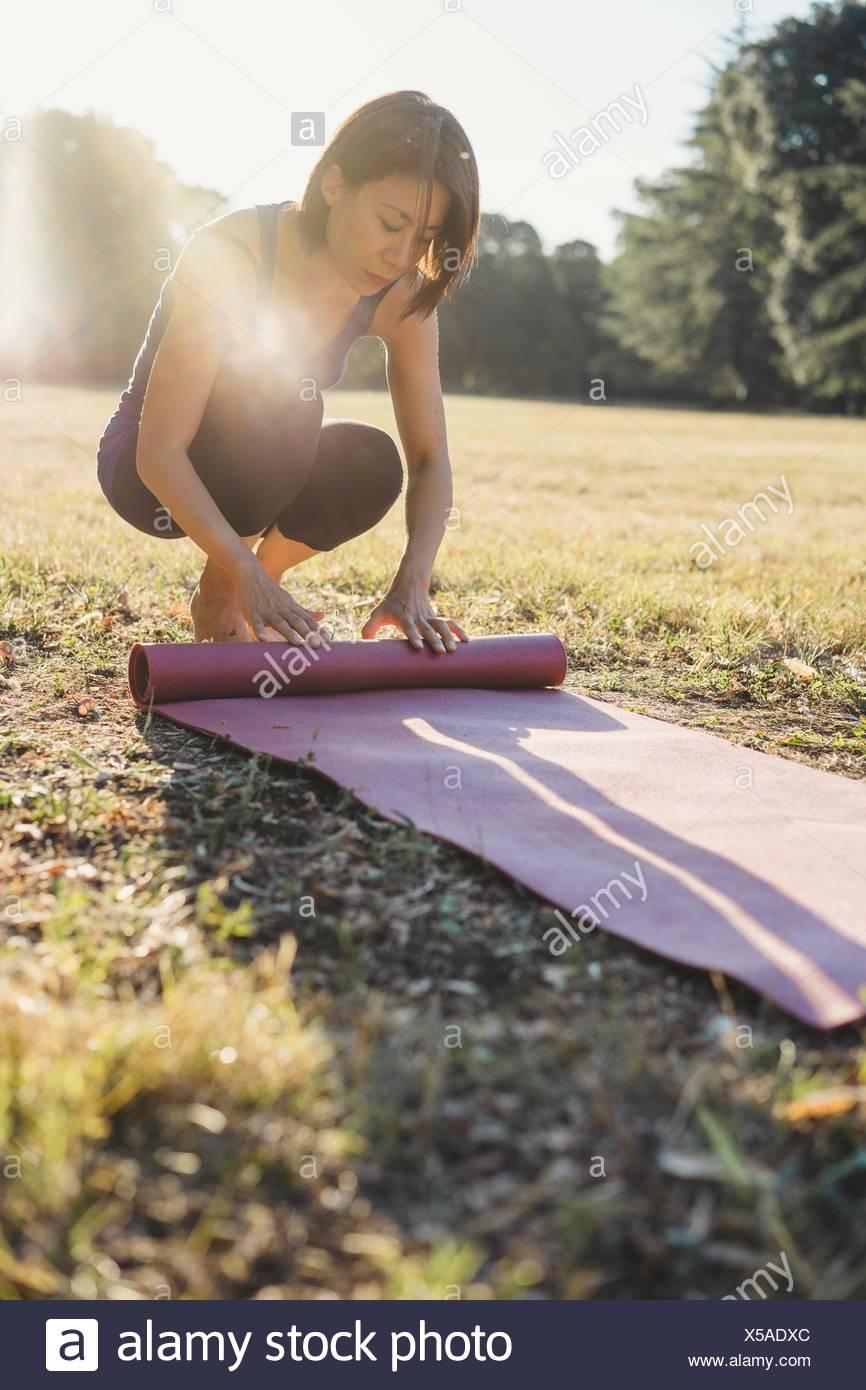 Mature Woman in park, roulant tapis de yoga Photo Stock