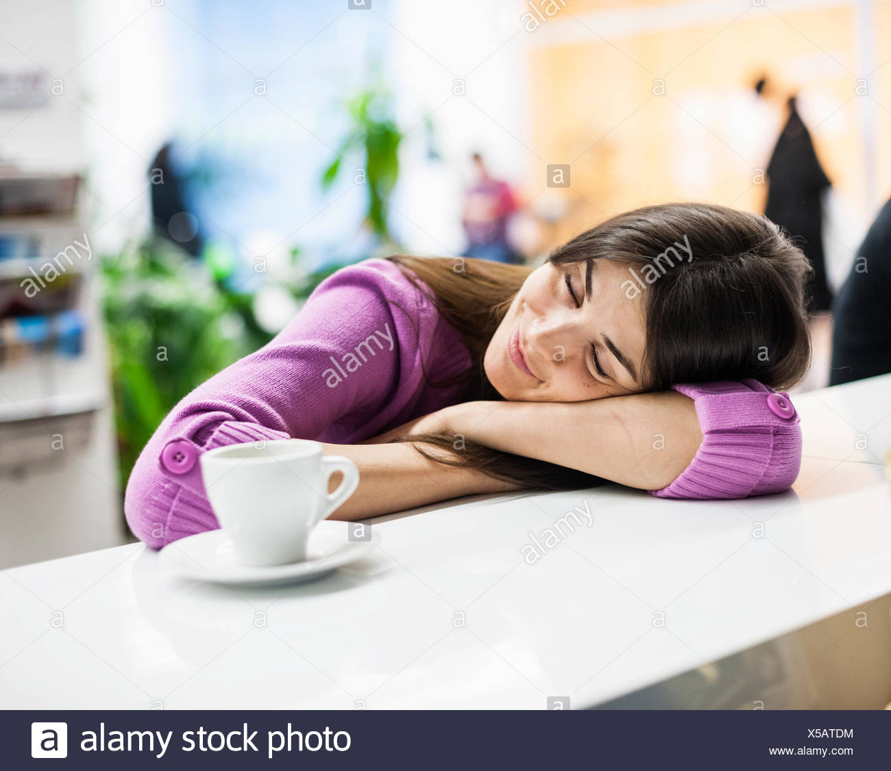 Young businesswoman sleeping at desk in office Photo Stock