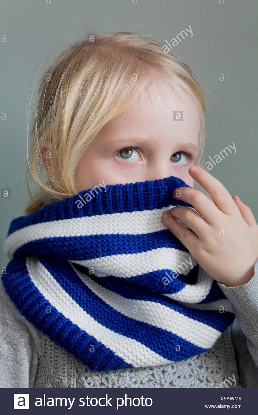 Fille de se cacher derrière son écharpe Photo Stock
