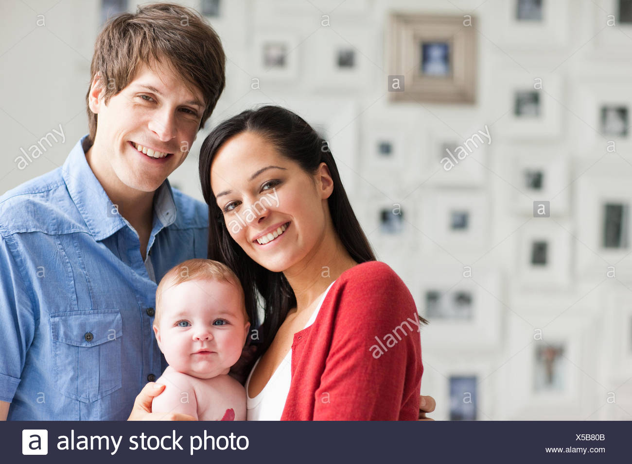 Smiling parents holding baby Photo Stock