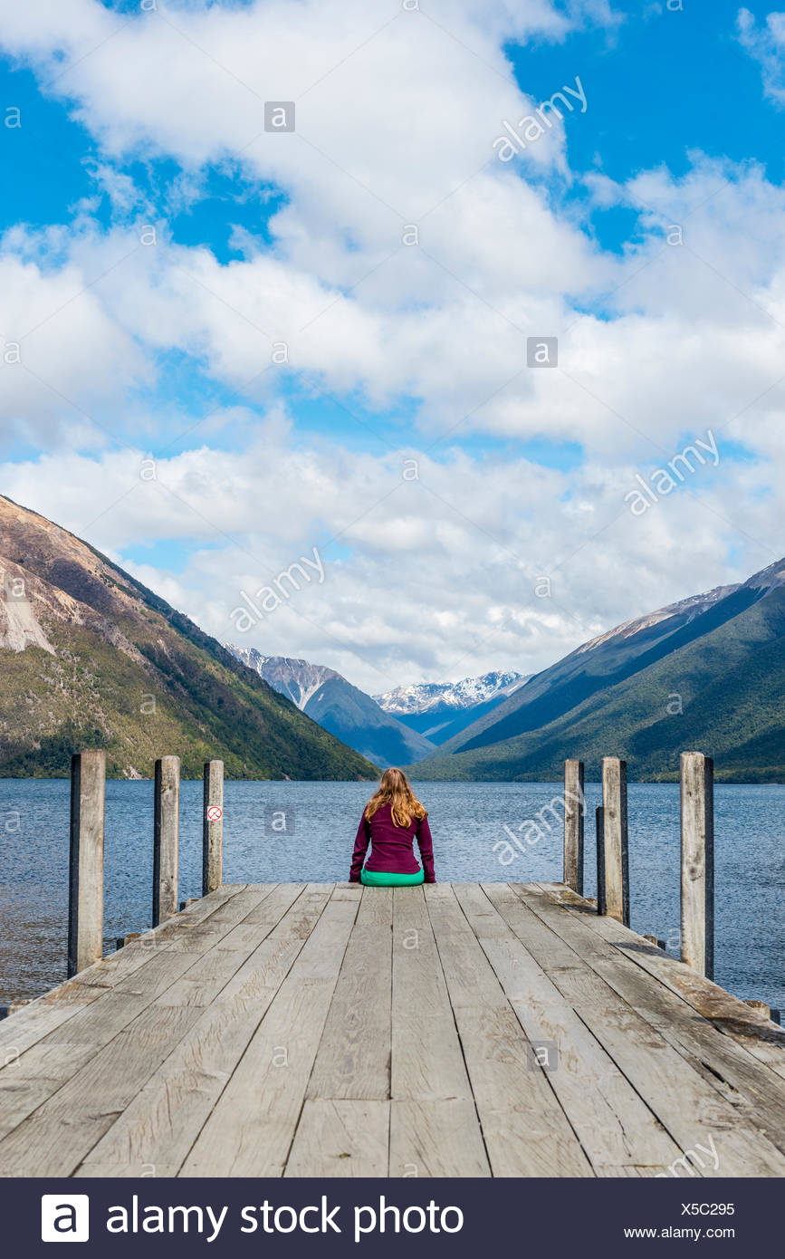 Femme assise sur un quai, vue du lac Rotoiti, Nelson Lakes National Park, district de Tasmanie, Southland, Nouvelle-Zélande Photo Stock