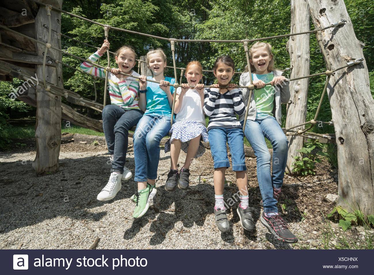 Les filles assis sur le pont de corde en aire de jeux, Munich, Bavière, Allemagne Photo Stock
