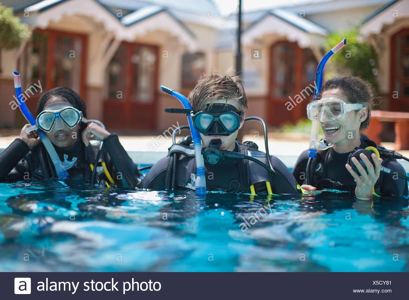 Trois jeunes plongeurs adultes en formation piscine Photo Stock