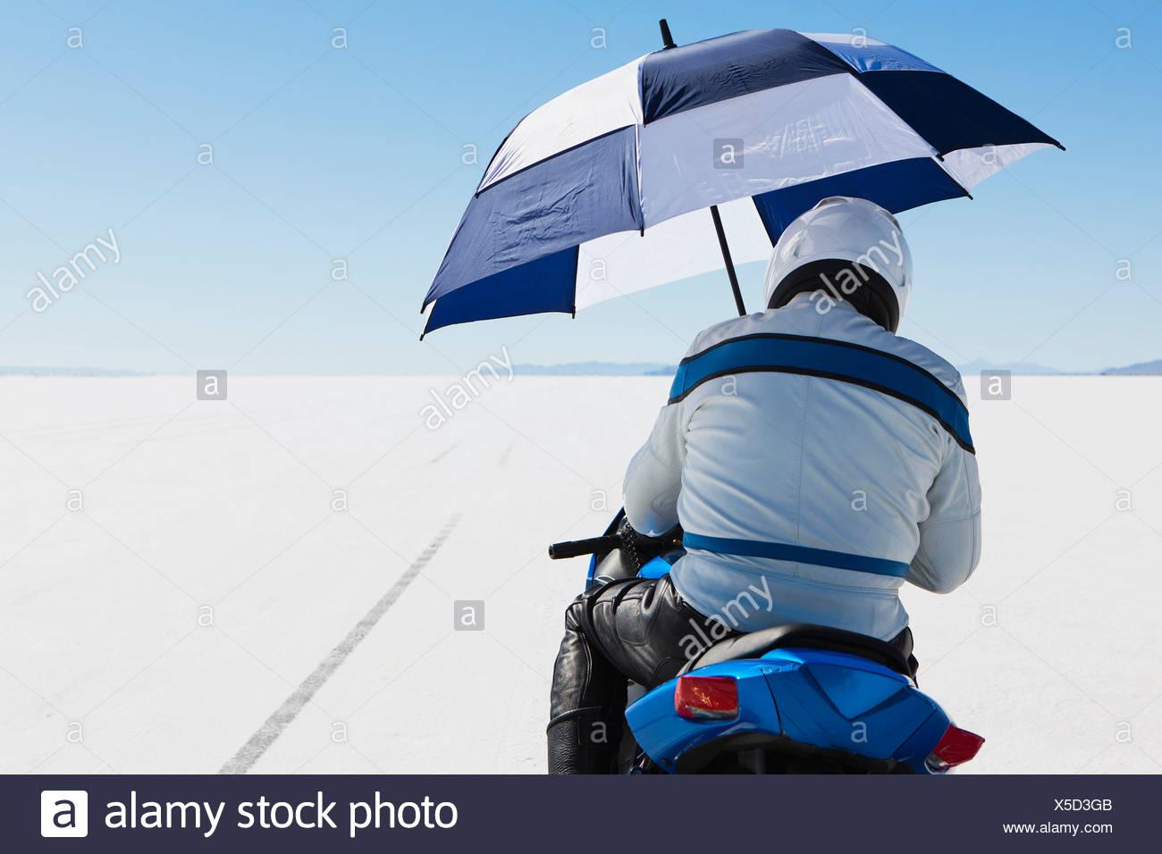 Un motocycliste s'abritant sous un parapluie, sur la ligne de départ au niveau de la semaine, sur la Bonneville Salt Flats. Photo Stock
