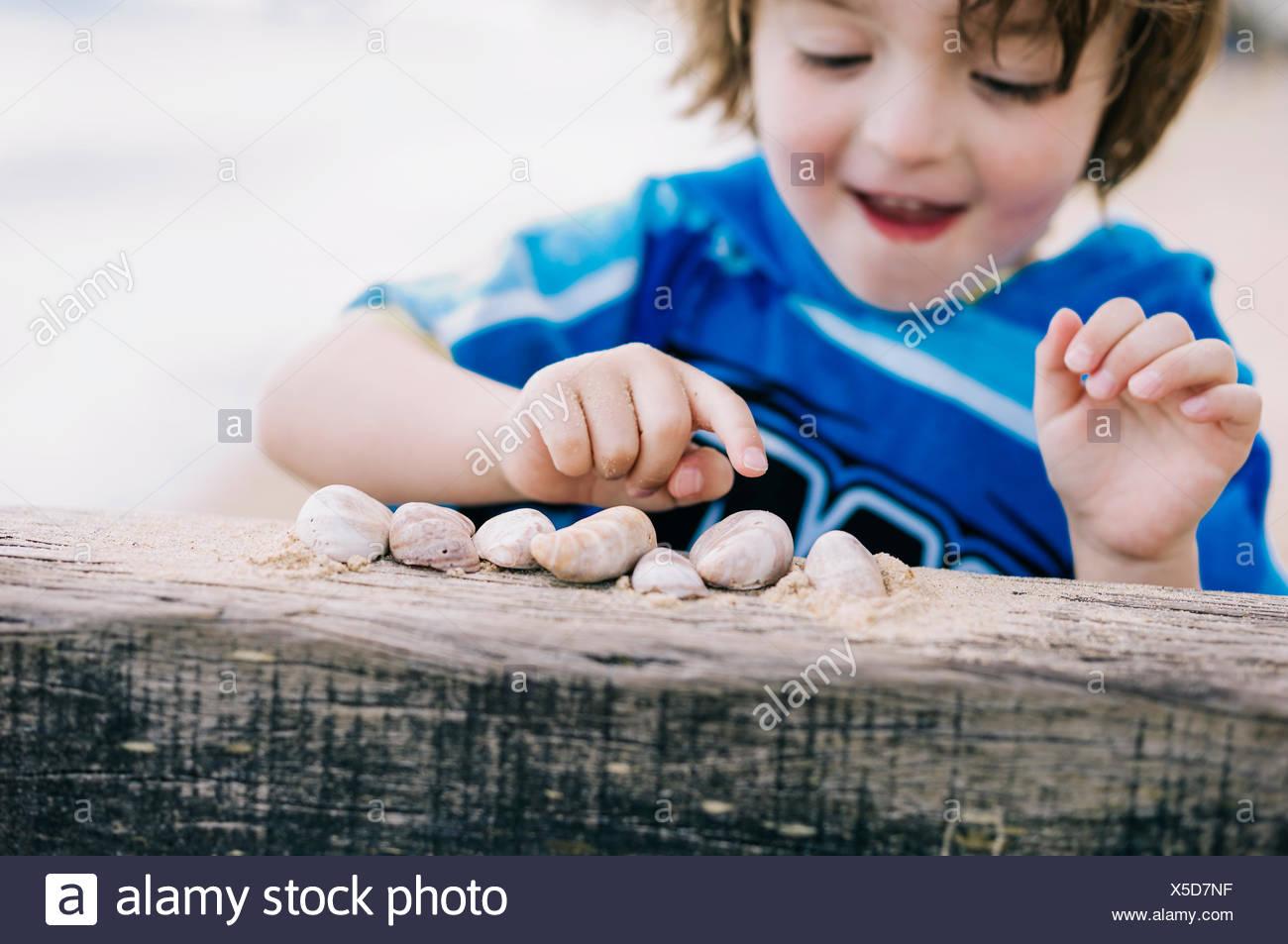 Un garçon à la plage en comptant les réservoirs alignés sur un brise-lames. Photo Stock