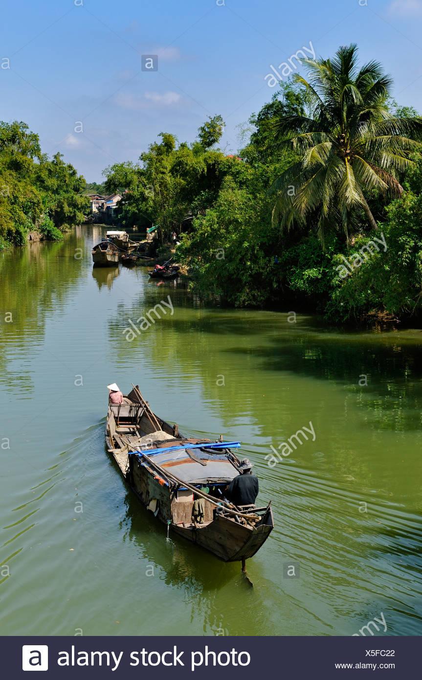 Petit bateau à moteur en passant par un canal d'eau entourée de végétation tropicale, Hue, Vietnam, Asie Photo Stock