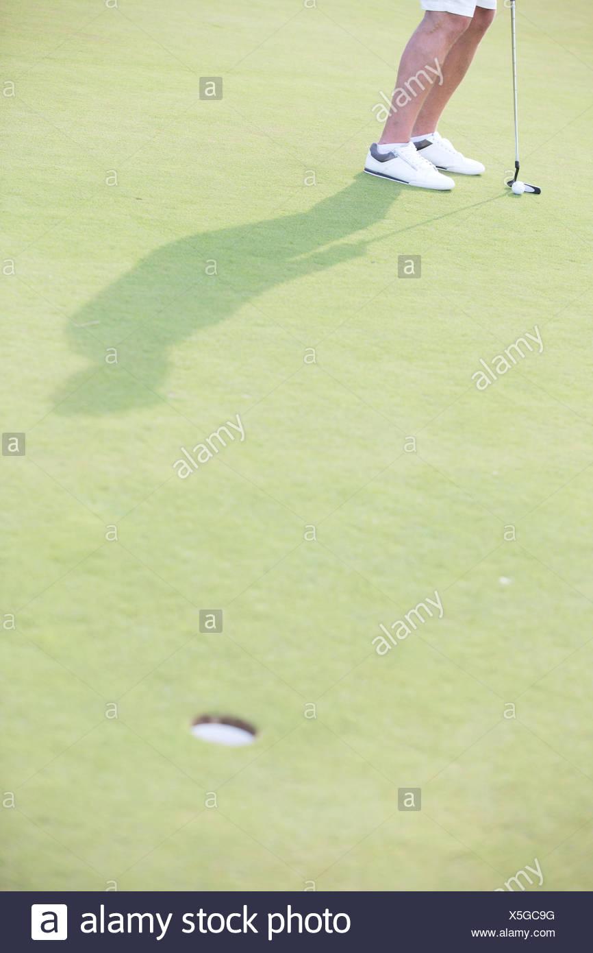 La section basse de l'homme d'âge moyen jouer au golf au cours Photo Stock