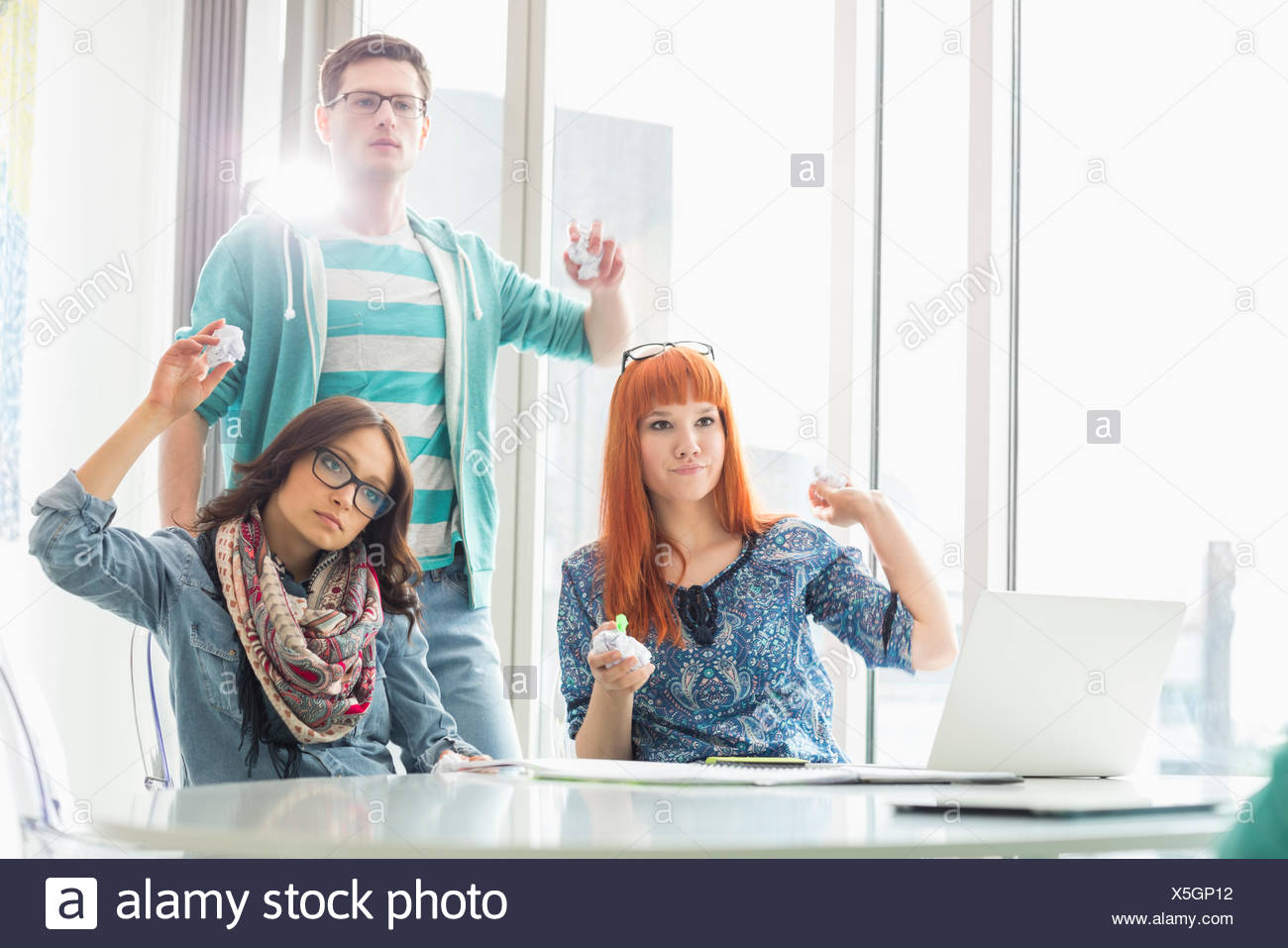 Angry woman throwing paper balls in creative office Photo Stock