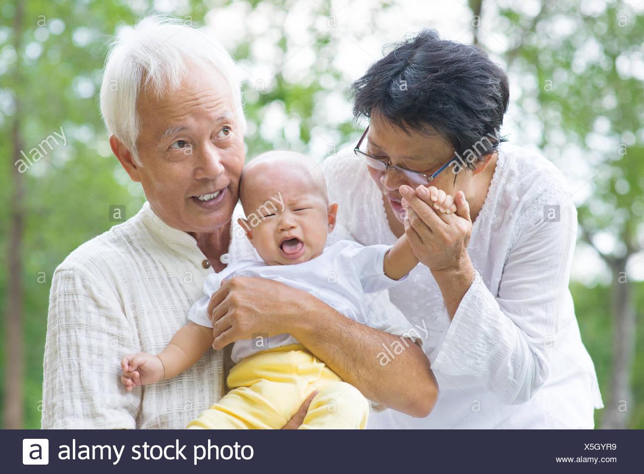 Bébé qui pleure asiatique réconfortés par les grands-parents au jardin extérieur Photo Stock