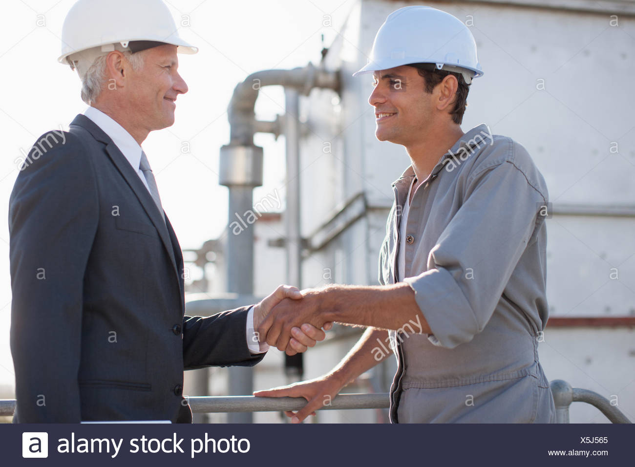 Businessman in hard-hat shaking hands with worker outdoors Photo Stock