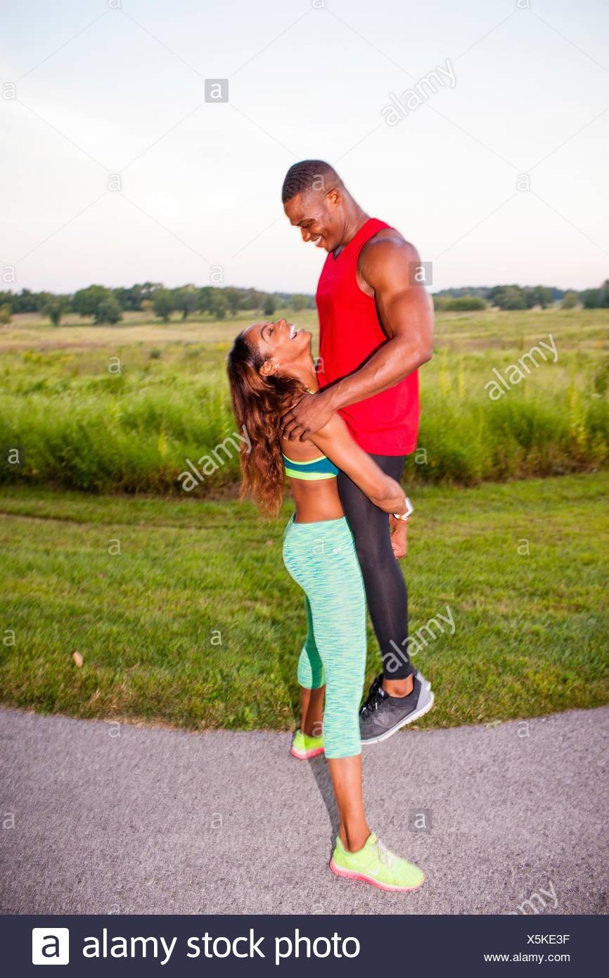 Jeune femme en soulevant petit ami formation Photo Stock