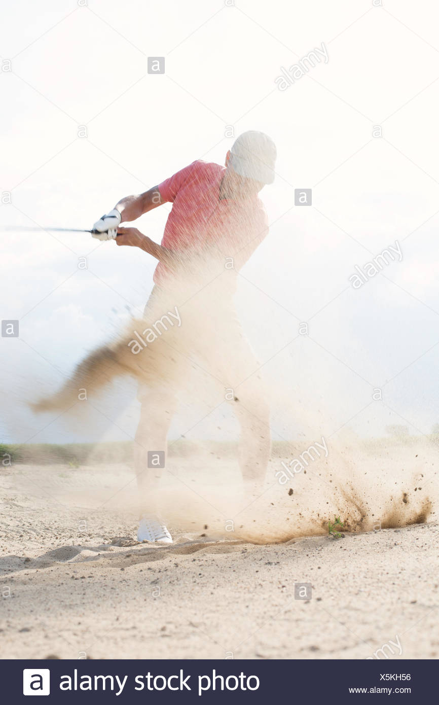 Homme d'âge moyen splashing sand tout en jouant au golf Photo Stock