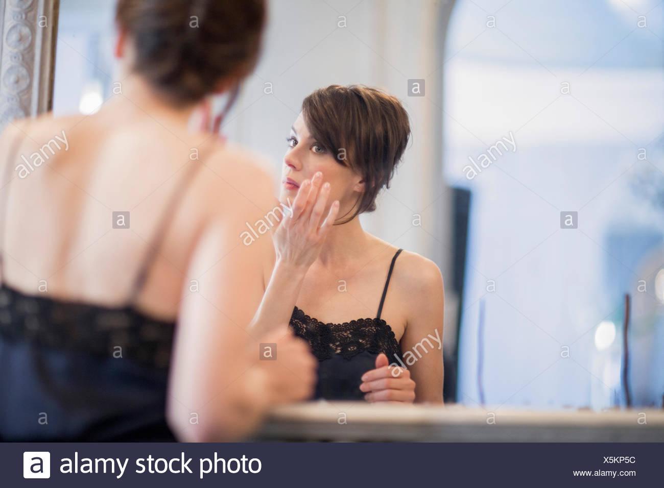 Femme l'application de crème anti-vieillissement sur son visage Photo Stock