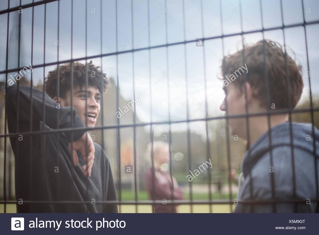 Deux jeunes hommes appuyé contre barrière, parler Photo Stock