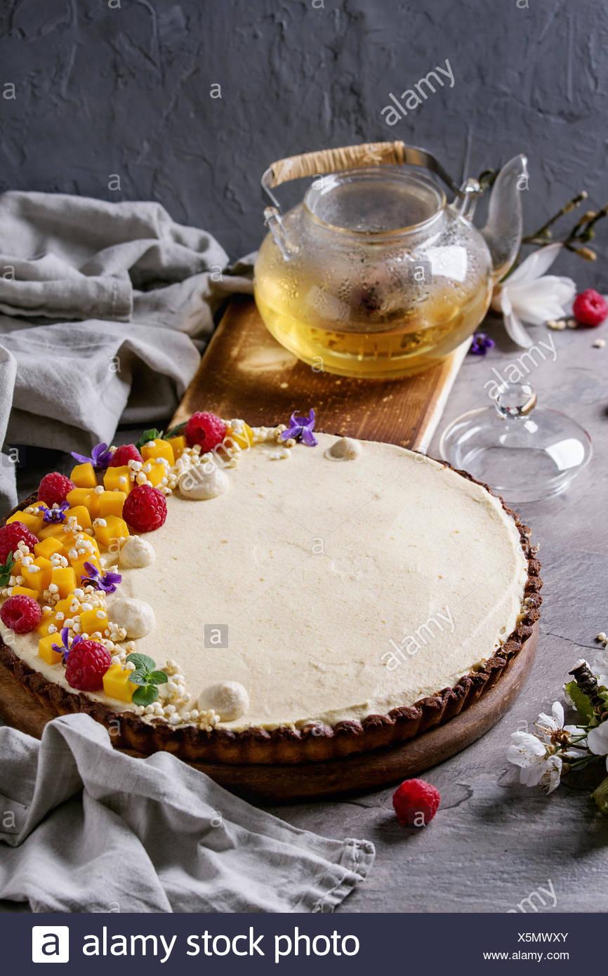 Tartelette au chocolat maison décorée par la mangue, framboises, menthe, riz soufflé et fleurs comestibles servi avec théière en verre textile et linge de maison sur tex gris Banque D'Images