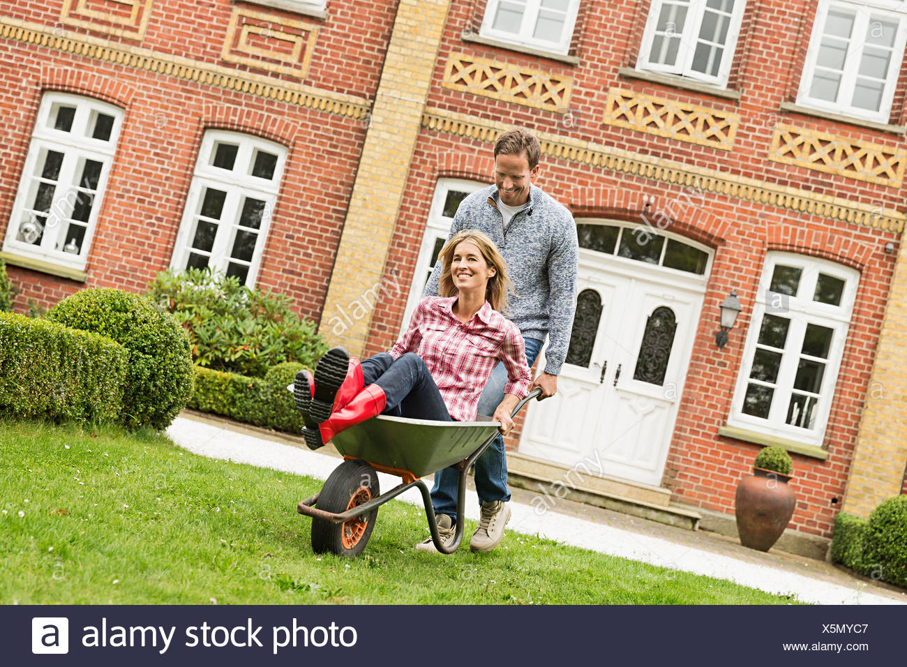 Mid adult man pushing woman in brouette Banque D'Images