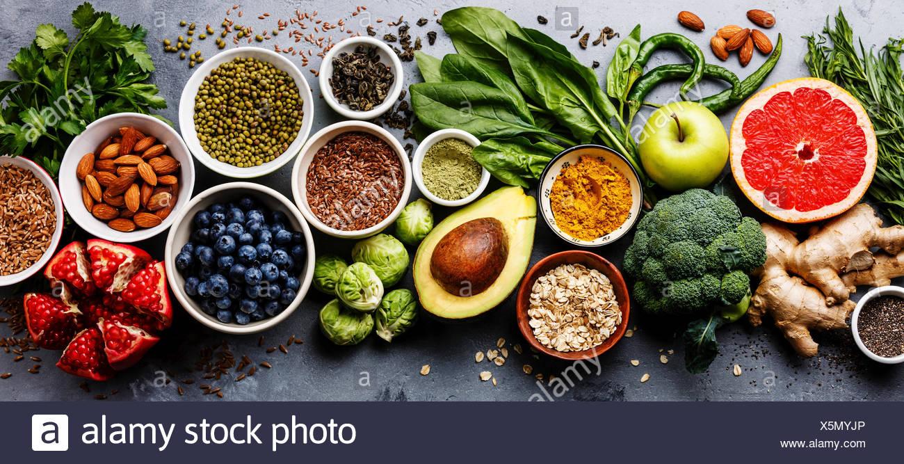 L'alimentation saine manger propre sélection: fruits, légumes, graines, superfood, céréales, légumes feuilles sur fond de béton gris Banque D'Images