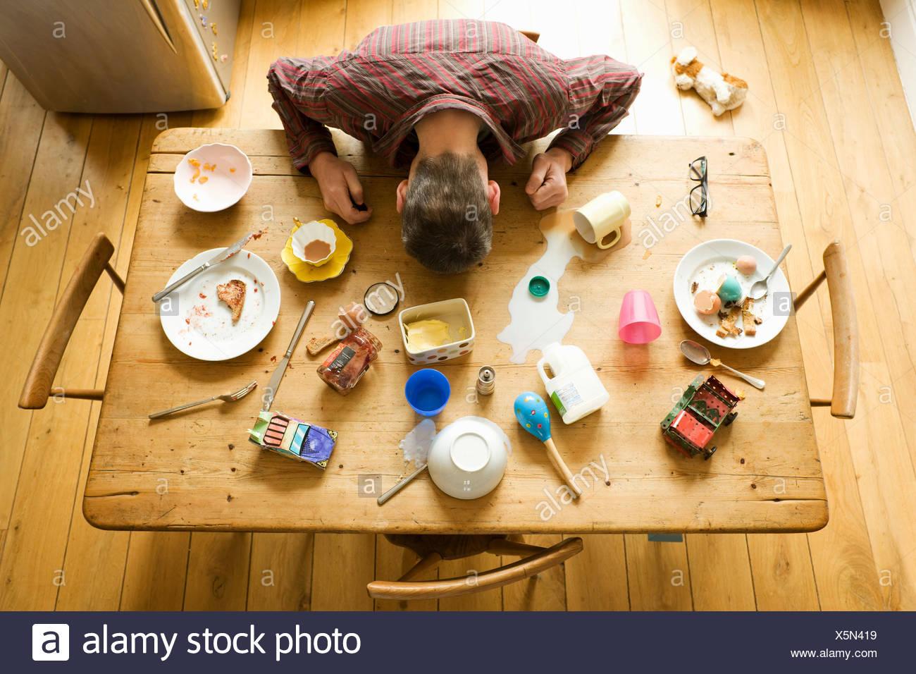 Vue de dessus de table de petit-déjeuner avec homme mûr entre les plaques en désordre Photo Stock