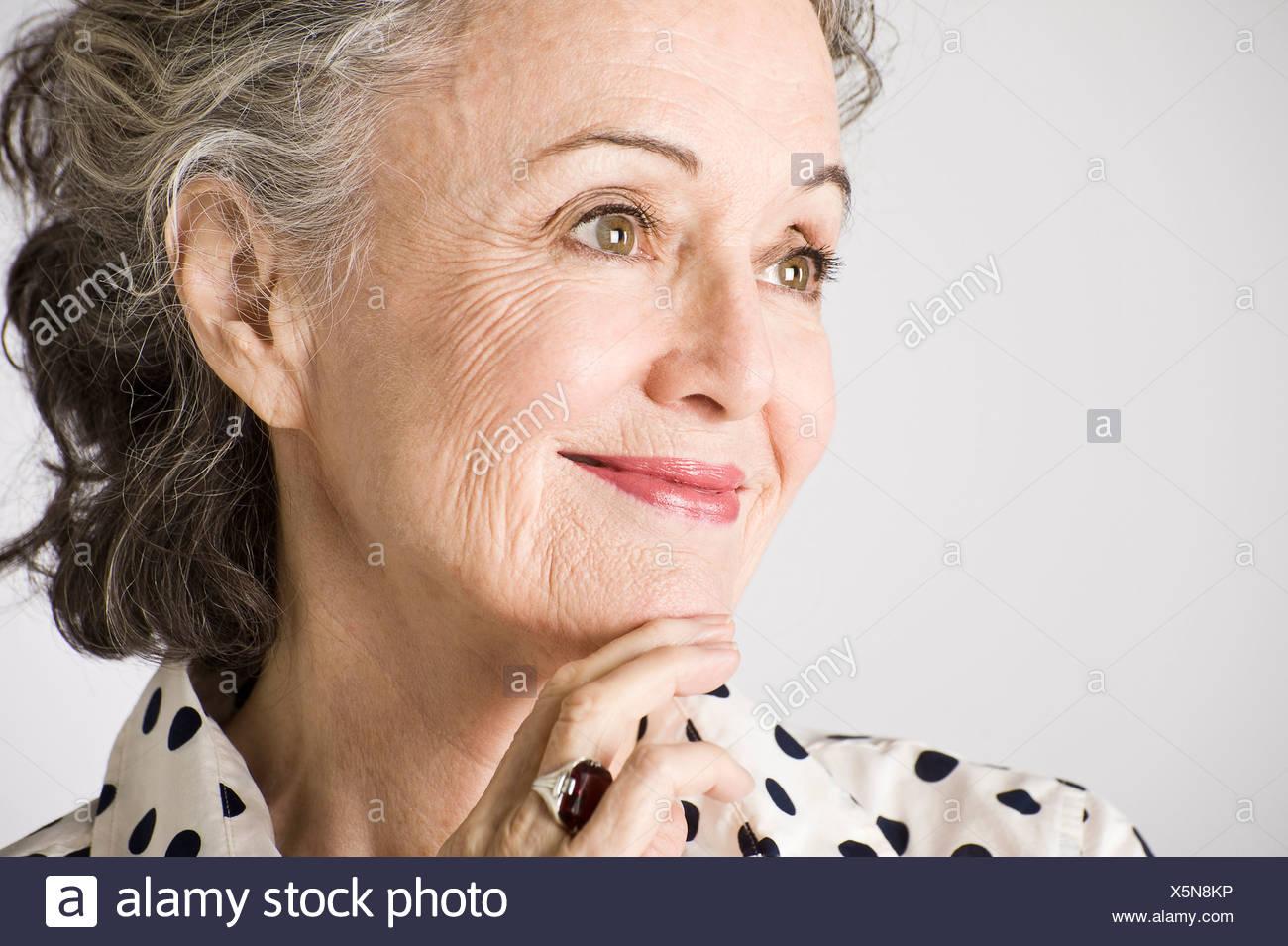 Portrait of senior woman, main sur le menton, smiling Photo Stock