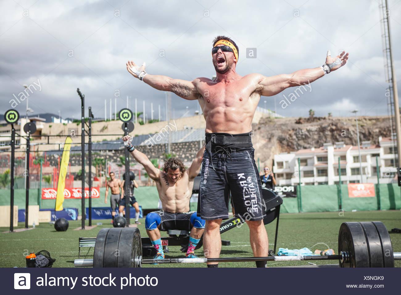 Les athlètes de l'équipe d'haltérophilie musclé torse nu en criant de joie après avoir remporté la compétition, tenerife, Îles Canaries, Espagne Photo Stock