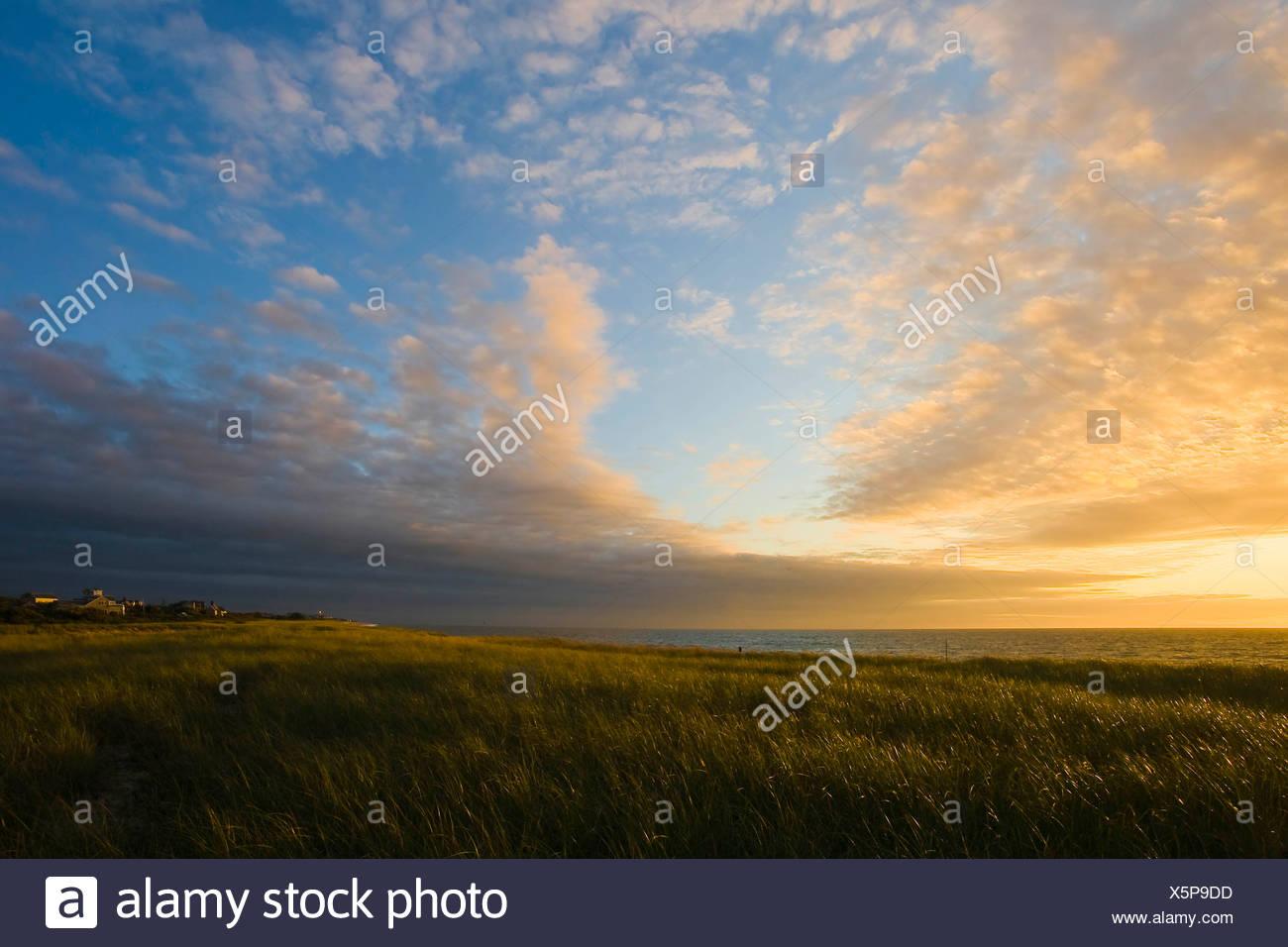 Les nuages se dissiper comme le soleil se lève sur la côte. Photo Stock