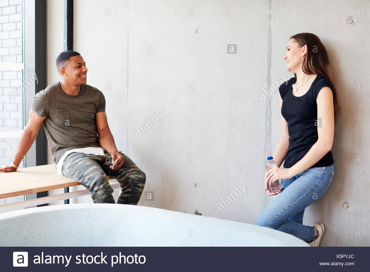 Les jeunes garçons et filles de flirter dans l'espace d'étude au Collège d'enseignement supérieur Photo Stock