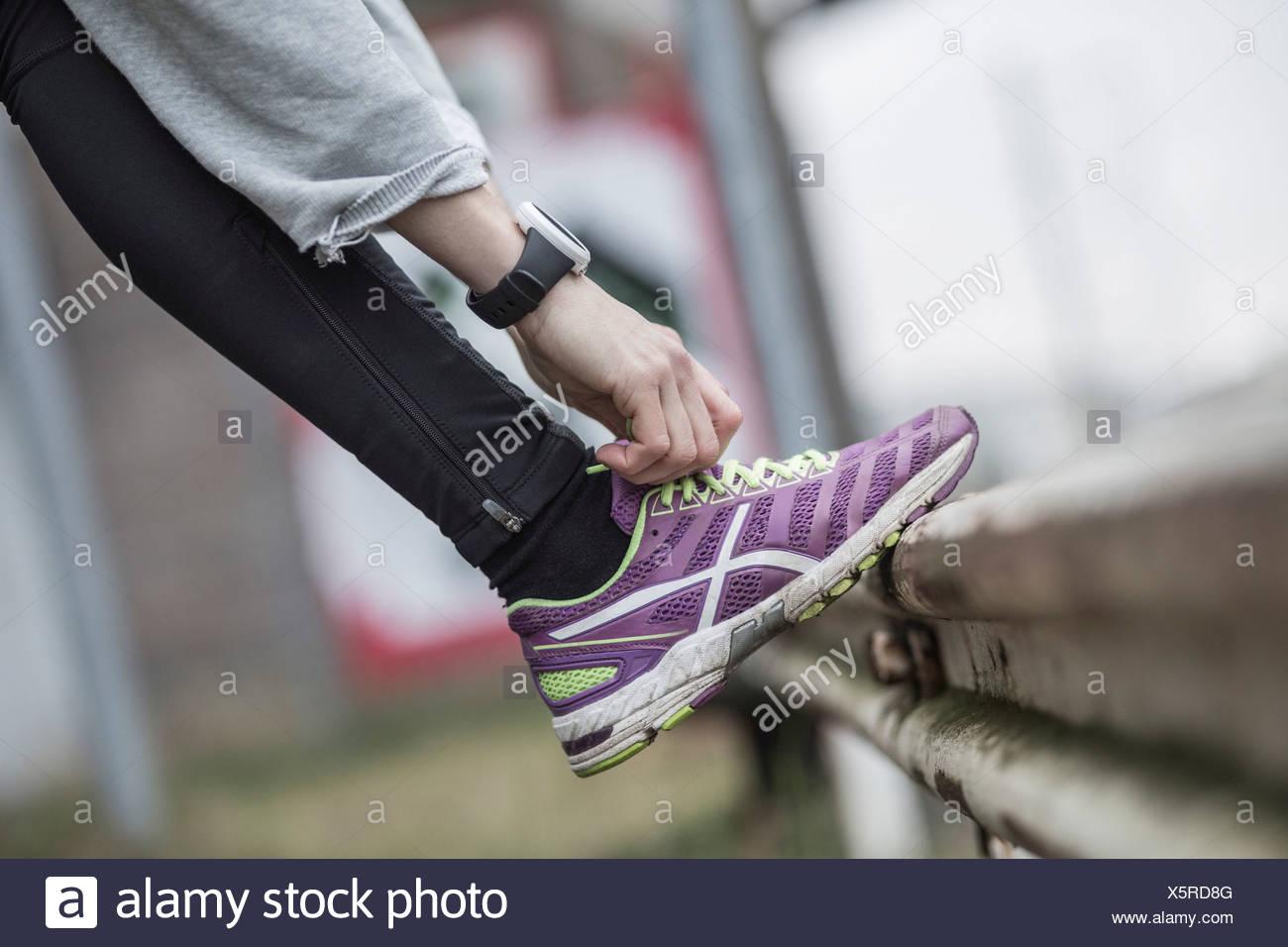 La section basse de femme dentelle de lier la chaussure de sport sur main courante Photo Stock